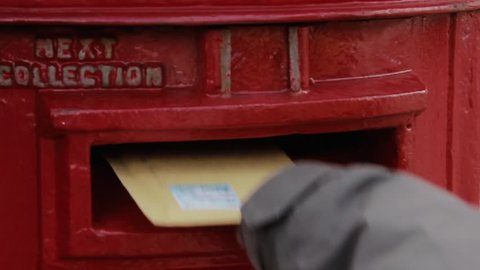 Stanley / Falkland Islands - 20 June 2017: Young Boy Posting a Letter in a Traditional Red Letter Box.