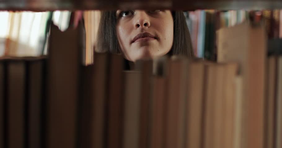 Female university student searching for book on bookshelves in library | Shutterstock HD Video #1024568615