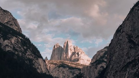 time lapse of the stunning Tre Cime Di Lavaredo mountain peaks in the Sexten Dolomites, Italy wedged between two cliff faces with clouds passing by creating sunshine and shadows