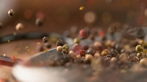 MACRO, DOF, SLOW MOTION: Fragrant colorful peppercorns bounce out of the metal frying pan after falling onto the table. Cool shot of pepper flakes and whole peppercorns falling along with a pan.