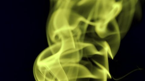 Thin trickle of bright neon yellow smoke slowly rising graceful twists up on black background. Colored smoke blowing from bottom to top. Closeup