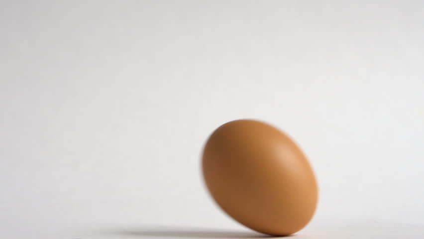 Egg are rolling on the white table. Easter eggs background. Can be used as looped.
