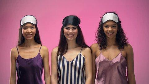 Smiling multiracial women in pajamas wearing eye masks, ready to sleep, relax