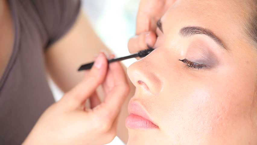 60d1f6d3b22 makeup artist applying mascara on eye lashes of model, close up