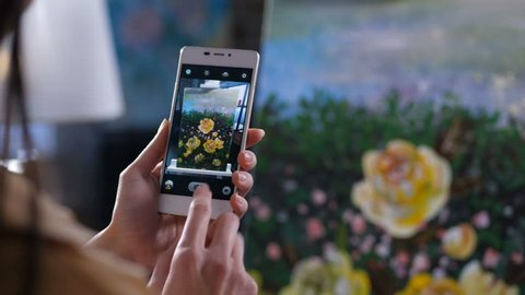 Close up hands of female painter holding cellphone photographing artwork on easel in home art studio. Artist hands holding mobile phone and making a picture o flowers painting on phone screen