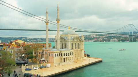 Aerial view of Ortakoy Camii, with a background view of Bosphorus Bridge on a cloudy day. Shot with Panasonic GH4 at UltraHD.