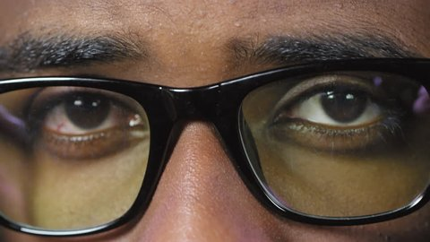 Extreme close up shot of young black man putting on stylish black rim glasses while looking at camera