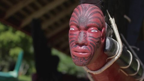 Closeup of the a maori sculpted head in the front of a traditional wooden boat in new zealand.