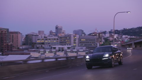 Portland, OR / USA Circa 2018 - Tracking shot of Porsche SUV driving on freeway bridge at dusk.