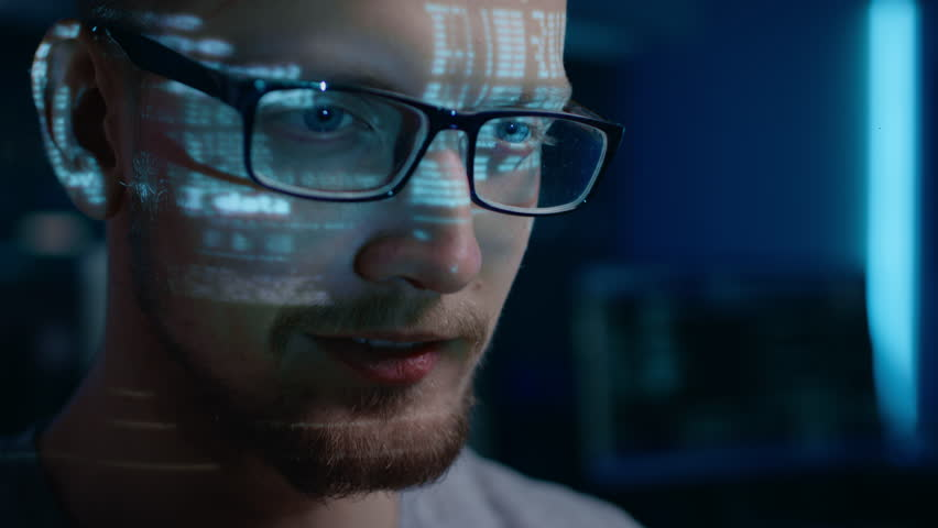 Portrait of Software Developer / Hacker wearing Glasses Working on Computer, Projected Code Numbers and Characters Reflect on His Face. Dark Room Full of Technology. Zoom in Shot | Shutterstock HD Video #1024746515