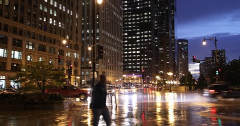 Chicago, Illinois, USA - September 25, 2018: Cars and people walk on the sidewalk along Wacker Drive in downtown Chicago Illinois USA during a rainy night