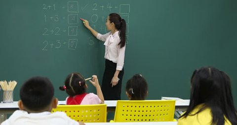 Asian teacher writing math problem on green board, student pay attention to her consciously, in math class.