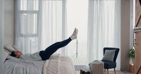 happy young woman jumping on bed resting after successful travel journey enjoying independent lifestyle freedom in hotel room