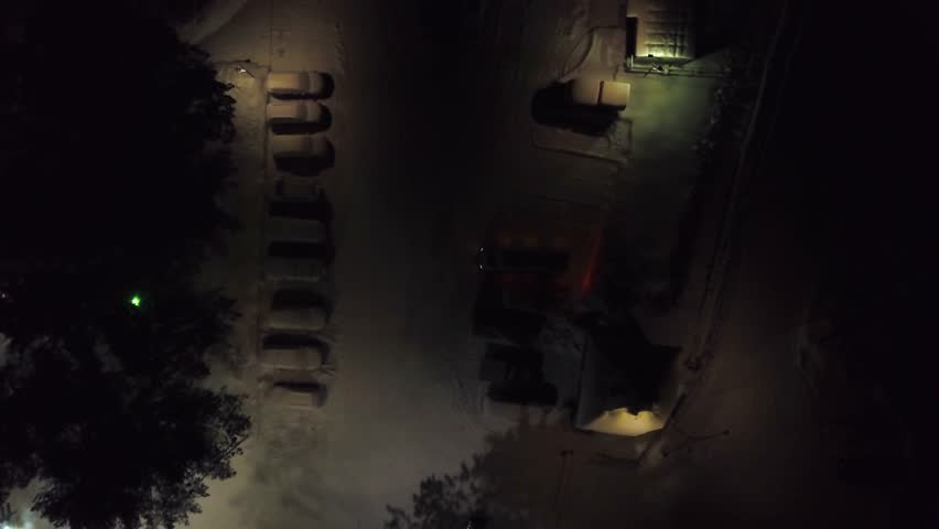 Top view of car park at night in winter. Clip. City parking with snow-covered cars and dim lighting at night in winter