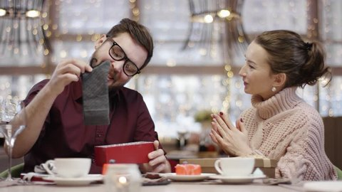 Adult man is taking socks out of gift box his wife gave to him and thanking her while sitting in a cafe