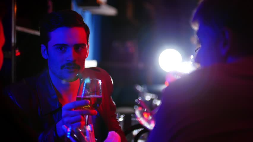 Company of friends sitting in bar, drinking beer and talking together | Shutterstock HD Video #1024844045