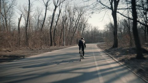 Professional Cyclist Riding Bike Fast.Professional Cyclist Ride On Road Bike. Cycling On Bicycle.Healthy Man Cycling Road Bicycle Outdoors Fitness Steadicam Shot.Active man Riding On Bicycle In Nature
