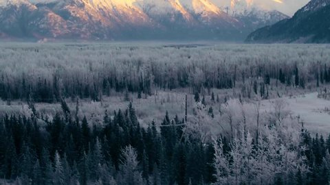 Snow covered forest in Alaska, aerial reveal of golden sunrise over Anchorage peaks 4k