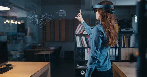 Young adult female using holographic augmented reality glasses in trendy office. Future concept. Generic big data interface added