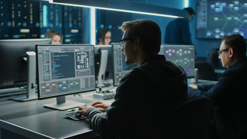 Team of IT Programers Working on Desktop Computers in Data Center Control Room. Young Professionals Writing on Sophisticated Programming Code Language