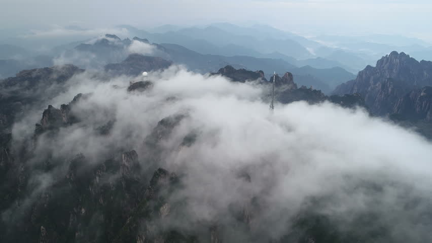 Drone shot of clouds enveloping the mountain ranges of Huangshan and its weather station, spectacular natural scenery in central China | Shutterstock HD Video #1025054555