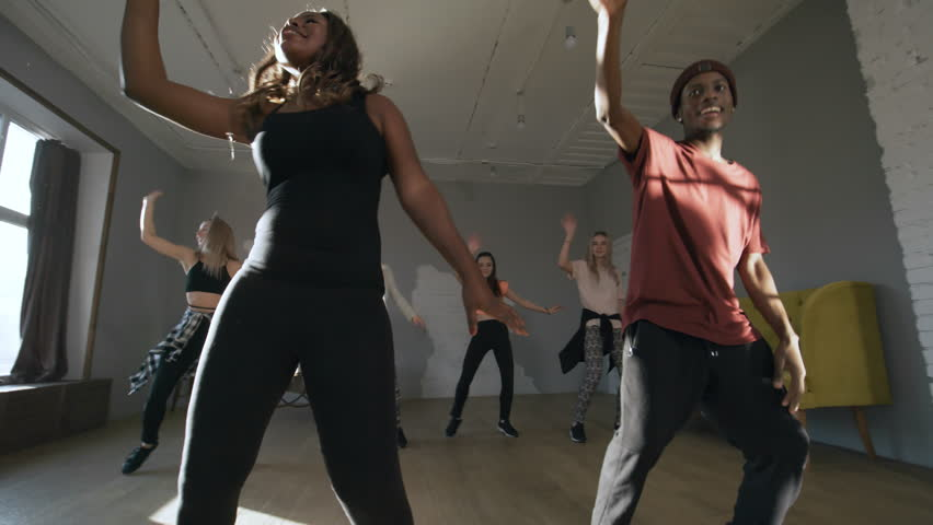Handheld tracking shot of happy black and Caucasian men and women moving to afro house music in sunny studio #1025073425