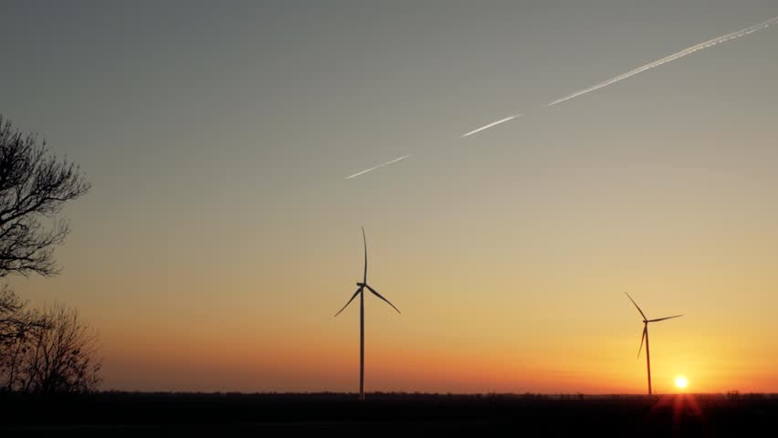 Wind turbines silhouettes at beautiful sunset against the backdrop of a flying plane in the sky   Shutterstock HD Video #1025082905