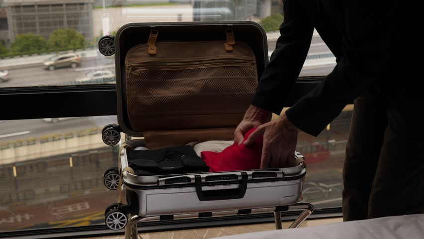 Man unpacking small suitcase, take out clothes and put on bed. Traveller check-in at hotel, move stuff out from bag. Plastic case lie on rack against window