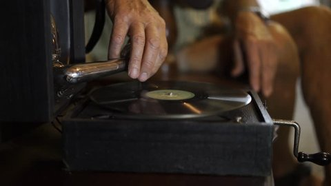 Hand of old man plays vintage records on antique gramophone.