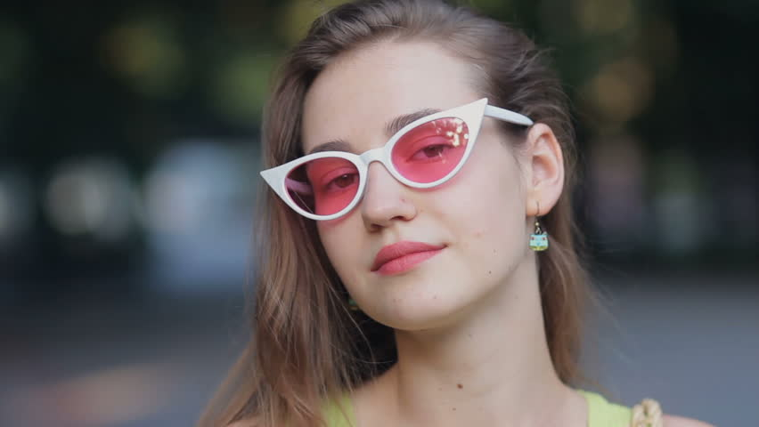 Close up portrait of attractive girl wearing pink sunglasses confident pretty looking at camera