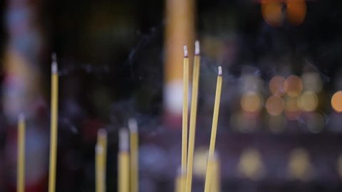 Slow motion panning shot across incense sticks burning in temple. Bokeh background lights from candles.