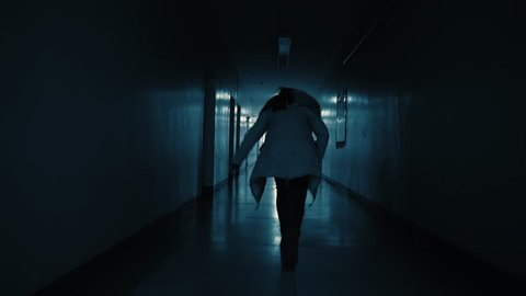 A young excited woman in a panic runs away from her pursuer along a dark corridor. A flickering sign with Russian text above the doors: exit.