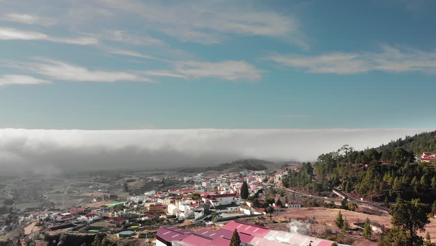 Aerial Hyperlapse A beautiful flight above the clouds over a small town with white houses and red roofs. In the frame of the mountain road hairpins serpentines are driven by cars. Mountainside with