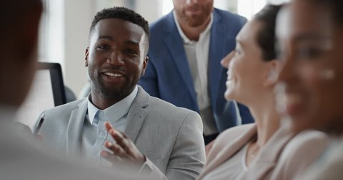 african american businessman chatting with colleagues in office meeting having conversation sharing ideas with diverse corporate group in workplace