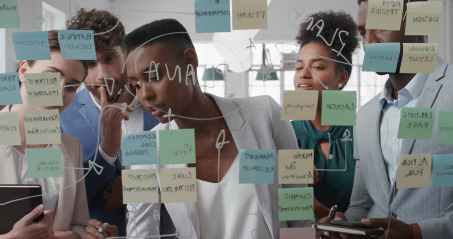 Corporate business people using sticky notes brainstorming problem solving strategy on glass whiteboard team leader woman showing solution for project deadline in office meeting | Shutterstock HD Video #1025208725