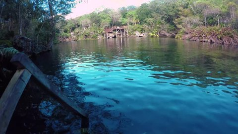 A view of the El Jardin del Eden cenote in the morning with swimmers.