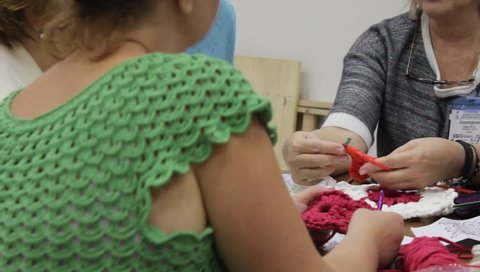 Odessa,Ukraine - December 22 2018: Close-up. Woman teacher  conducts the women a masterclass on crochet lace or clothing. Taken from a moving camera on a slider. Camera dolly