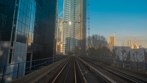 LONDON, circa 2019 - A frantic POV hyperlapse of a train journey along the Canary Wharf Docklands District of London, England, UK on a sunny day