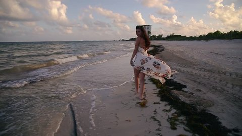 A happy young brunette woman walking, running, and playing on a tropical beach near Cancun, Mexico at sunset.