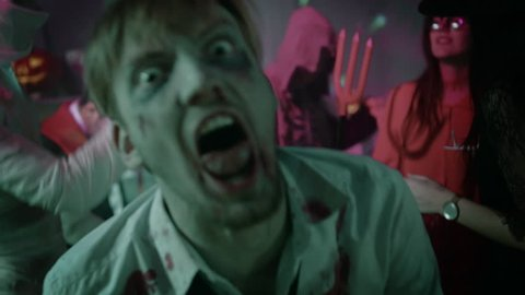 Halloween Costume Party: Brain Dead Bloody Zombie Turns Around and Attacks. In the Background Zombie, Death, Witch, Mummy and She Devil Have Fun in a Monster Party Decorated Room. Shot on 8K RED