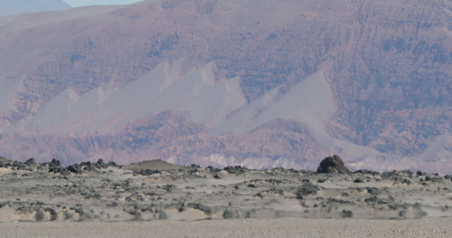 Close up of heat haze effect on black bed of lava floor. Desert color layer mountains at background. Antofagasta de la Sierra, Catamarca, Argentina | Shutterstock HD Video #1025346995
