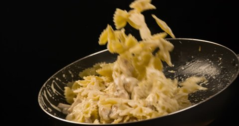Cooking Pasta with champignons mushrooms tossing in Pan Slow motion 4K video