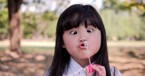 Young beautiful girl are blowing bubble with funny face at park. 4k Resolution. Slow motion shot.