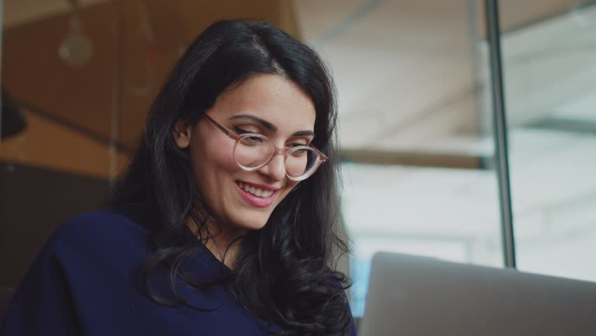 Happy young businesswoman in trendy glasses using modern laptop working in creative agency sitting at co working office, shot on Cinema Camera 4K #1025447975