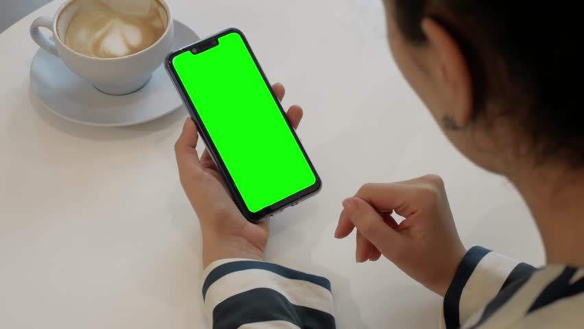 A woman is talking to a friend over a video call on a green-screen smartphone. A girl in a cafe with a cup of coffee on the table and a phone with chroma key talks online | Shutterstock HD Video #1025452925
