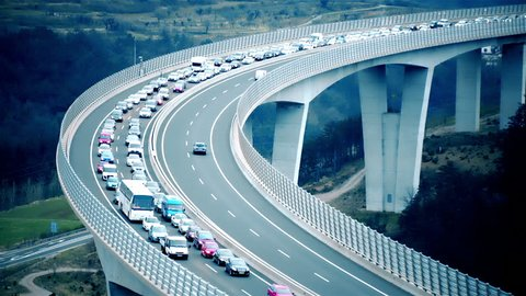 Traffic jam on highway bridge. Static long shot of the bridge in focus while traffic jammed and not moving. Beautiful landscape scenery.