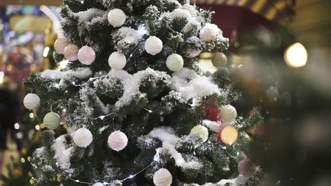 Gimbal tilt up shot of artificial christmas green tree with artificial snow decorated with white, green and red christmas tree balls indoors.