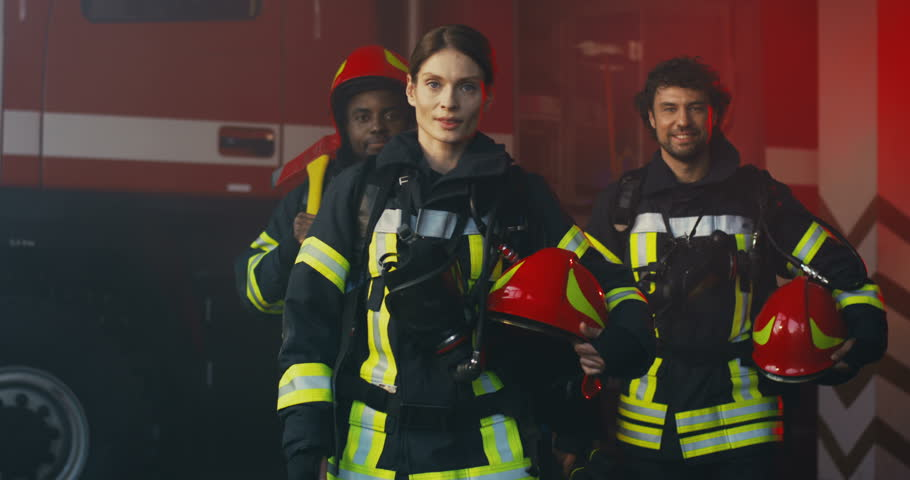 Mixed races team of fire fighters two men and woman walking in the full equipment with helmets in hands and smiling to the camera at their station. | Shutterstock HD Video #1025529875