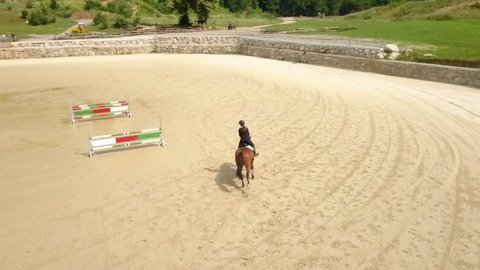 We can see a big horse arena outdoors and a young student is galloping. Aerial shot.
