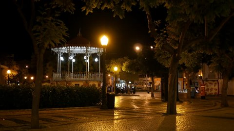 Faro, Portugal - September 4 2017: Town square at night with illuminated bandstand and reflections on cobbled street in Faro, Algarve, Portugal